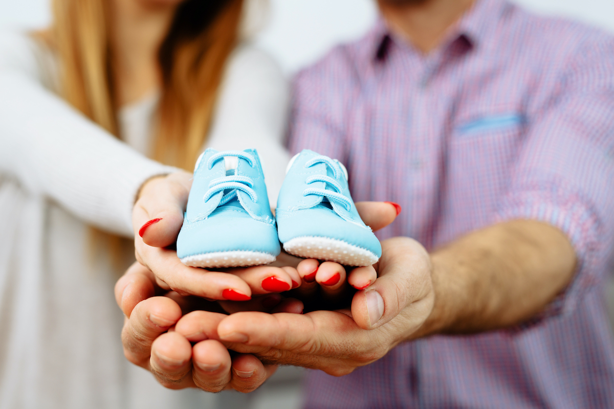 Expecting couple holding light blue baby shoes